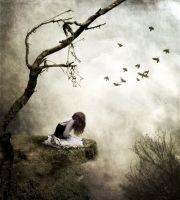 Сумна дівчина сидить на скелі