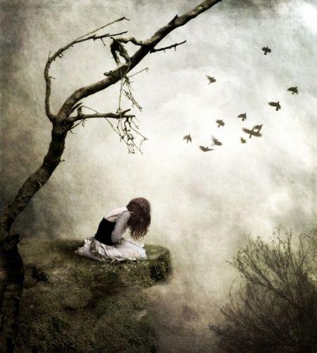 Печальная девушка сидящая на скале